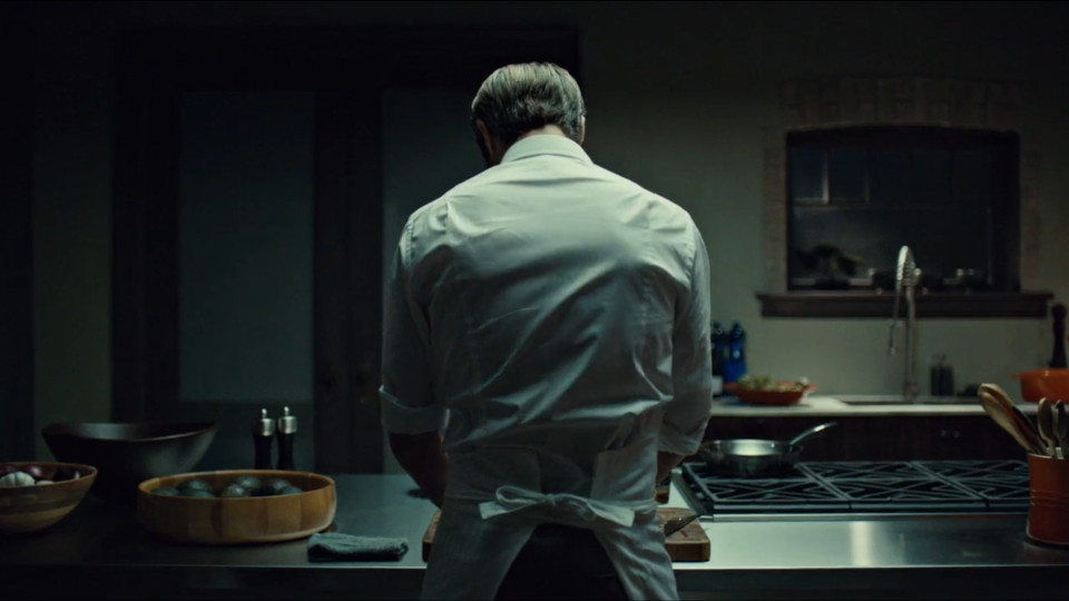In a dark kitchen, Hannibal's white shirt and apron is illuminated from above. There are pieces of cookward around him, and he is leaning over a cutting board.